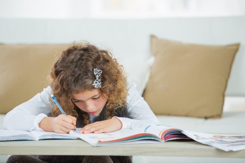 Cute girl doing homework for school stock photography