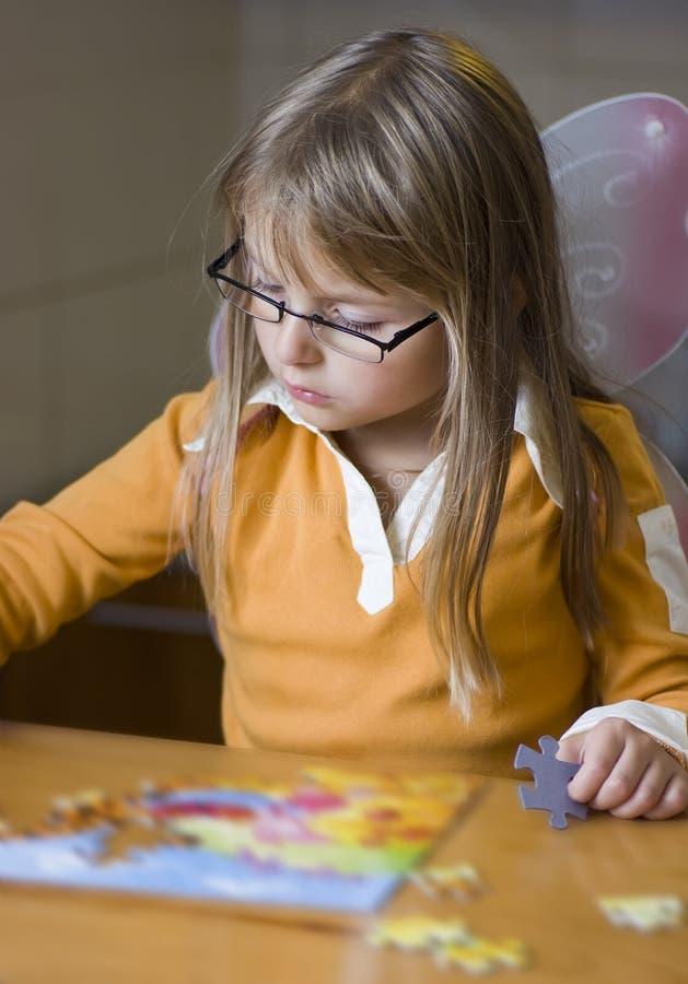 Cute girl doing jigsaw puzzle. A cute blonde girl doing jigsaw puzzle stock photos