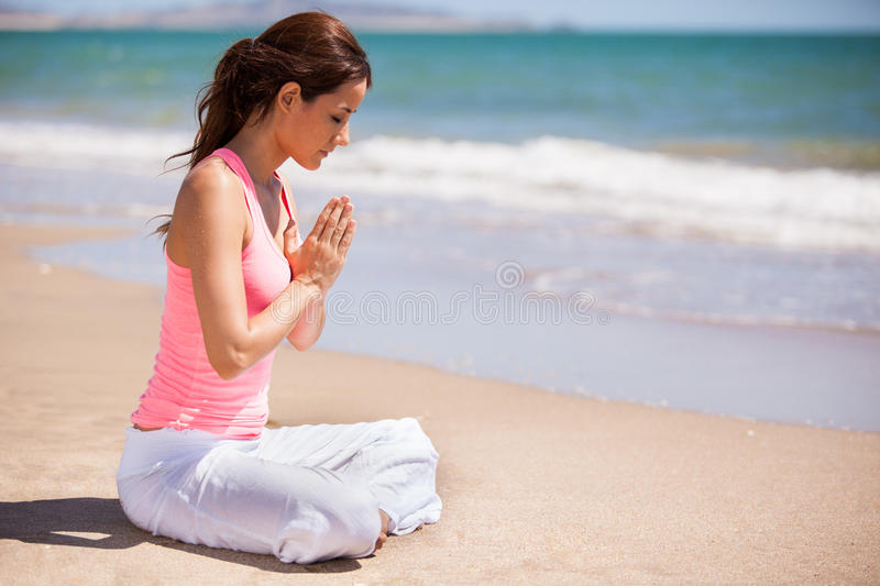 Cute girl doing some meditation. Gorgeous young woman meditating and practicing yoga at the beach royalty free stock photos