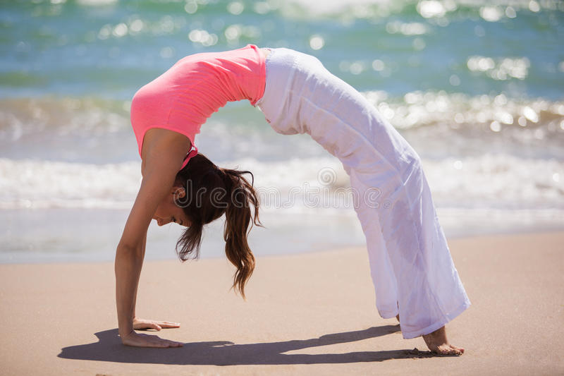 Cute girl doing yoga at the beach. Beautiful young woman arching her back and standing backwards on hands and feet while doing yoga at the beach stock photography