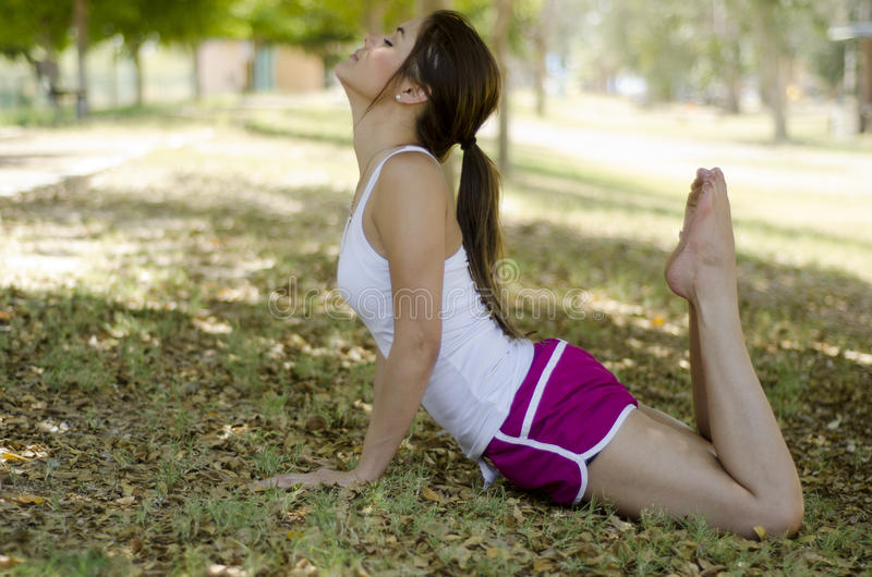 Cute girl doing yoga at a park. Pretty young girl meditating and doing yoga at the park royalty free stock photo