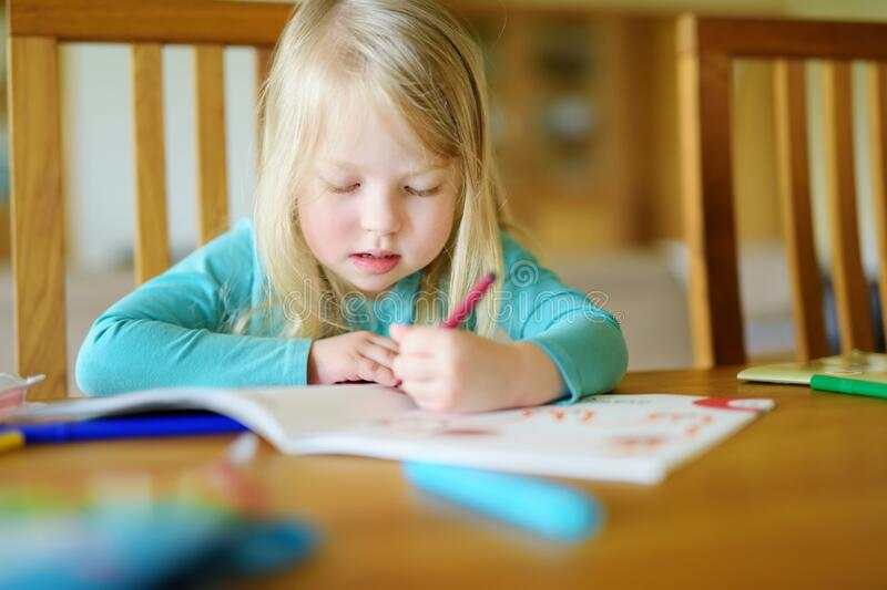 Cute girl drawing with colorful pencils at a daycare. Creative kid painting at school. Girl doing homework at home stock photography