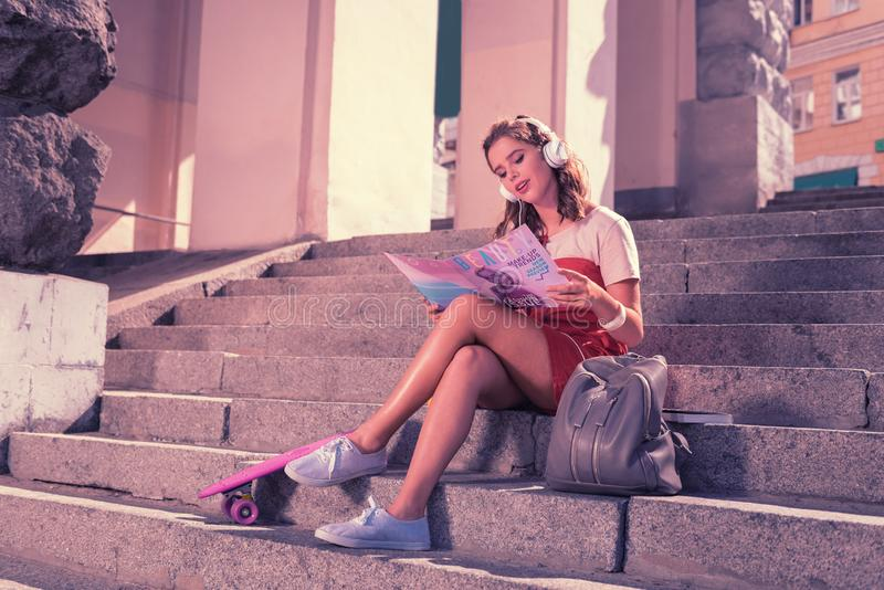 Cute girl dreaming of becoming model reading fancy fashion magazine royalty free stock photos