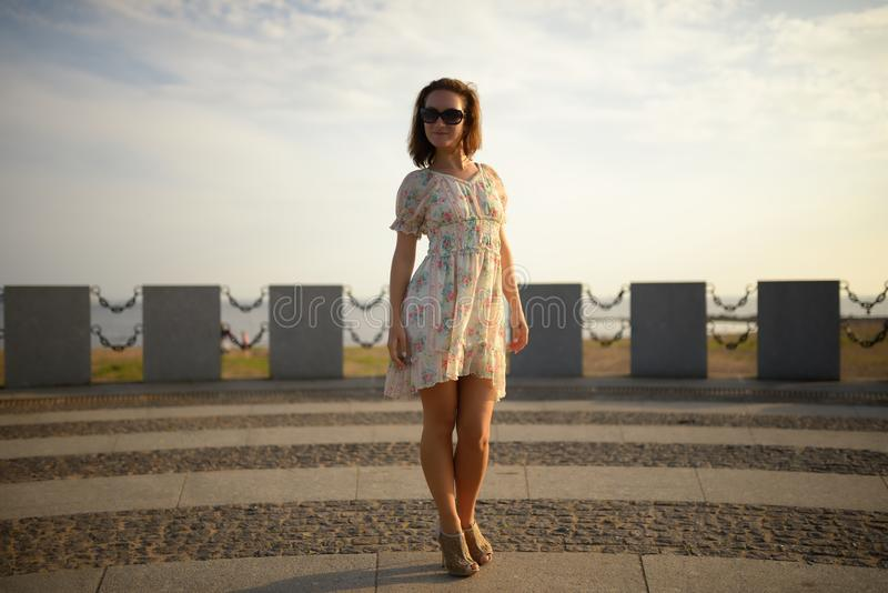 Cute girl in dress posing on square. Sunset stock photo