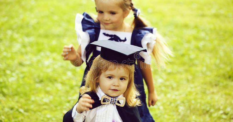 Cute girl dressing small boy in graduation hat and robe. Cute little girl with long hair in blue dress dressing adorable small boy in black graduation hat or cap royalty free stock photography