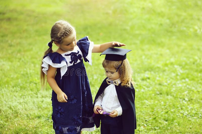 Cute girl dressing small boy in graduation hat and robe. Cute little girl with long hair in blue dress dressing adorable small boy in black graduation hat or cap royalty free stock images