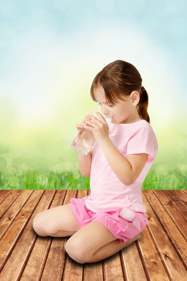 Cute girl drinking water stock photos