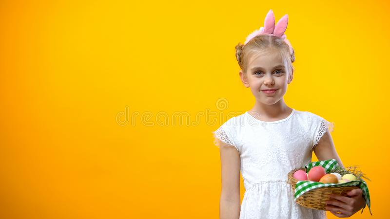Cute girl in ears looking at camera, holding eggs basket, art school for young royalty free stock photography