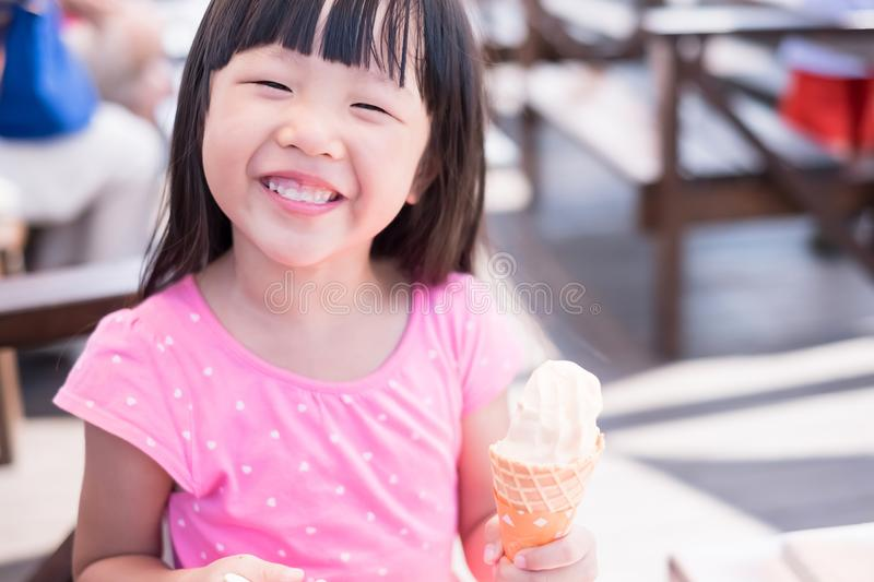 Cute girl eat ice cream. And smile happily royalty free stock photography