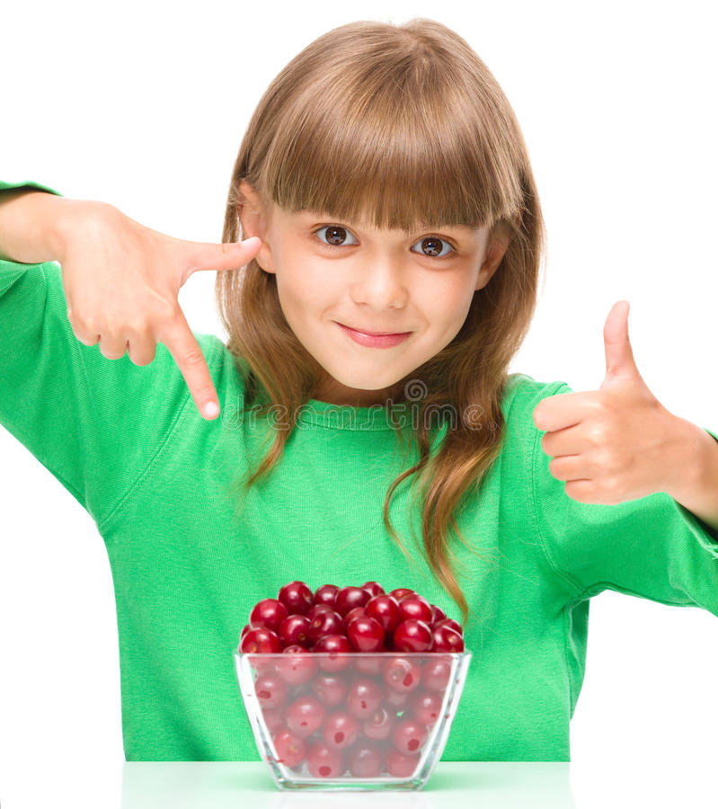 Cute girl is eating cherries showing thumb up sigh. Cute girl is eating cherries and showing thumb up sigh, isolated over white royalty free stock image