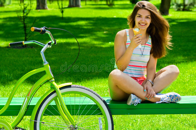 Cute girl eating ice cream after cycling cruiser royalty free stock photography