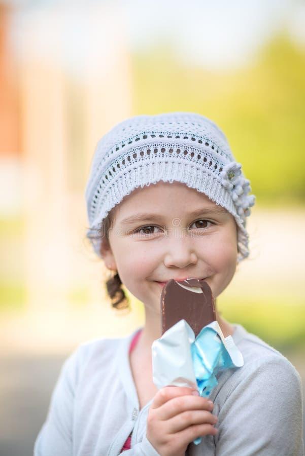 Cute girl eating ice-cream. On the street stock photos