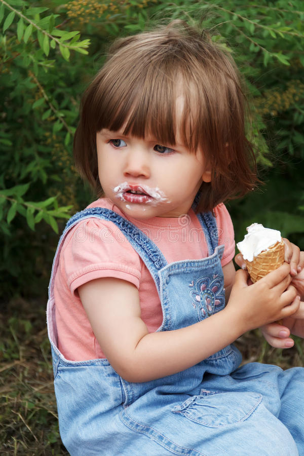 Cute girl are eating icecream. In hands royalty free stock photo