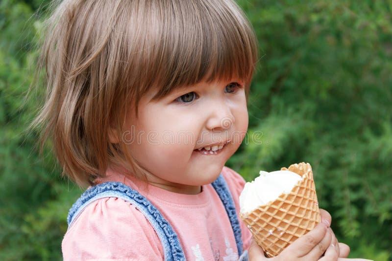 Cute girl are eating icecream. Horizontal photo of cute girl are eating icecream in summer time royalty free stock image