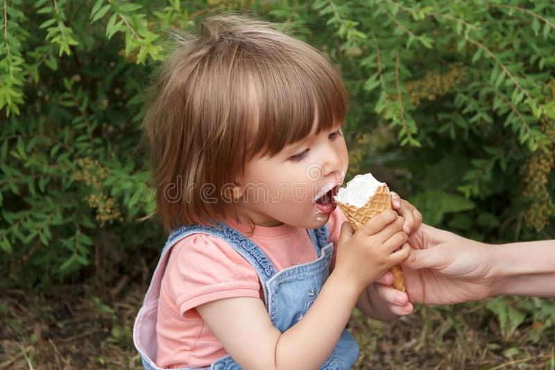 Cute girl are eating icecream. Photo of cute girl are eating icecream in summer time stock image