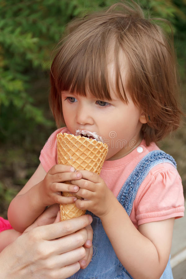 Cute girl are eating icecream. Photo of cute girl are eating icecream in summer stock photography