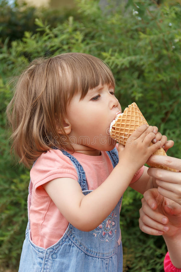 Cute girl are eating icecream. Vertical photo of cute girl are eating icecream in summer time stock photo