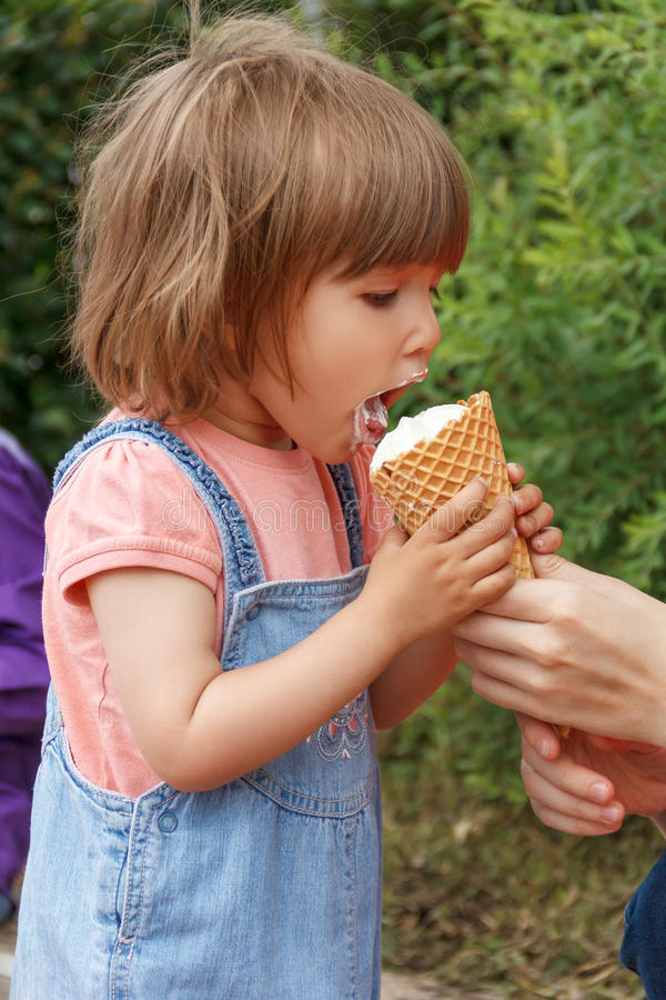 Cute girl are eating icecream. Vertical photo of cute girl are eating icecream in summer time stock photography