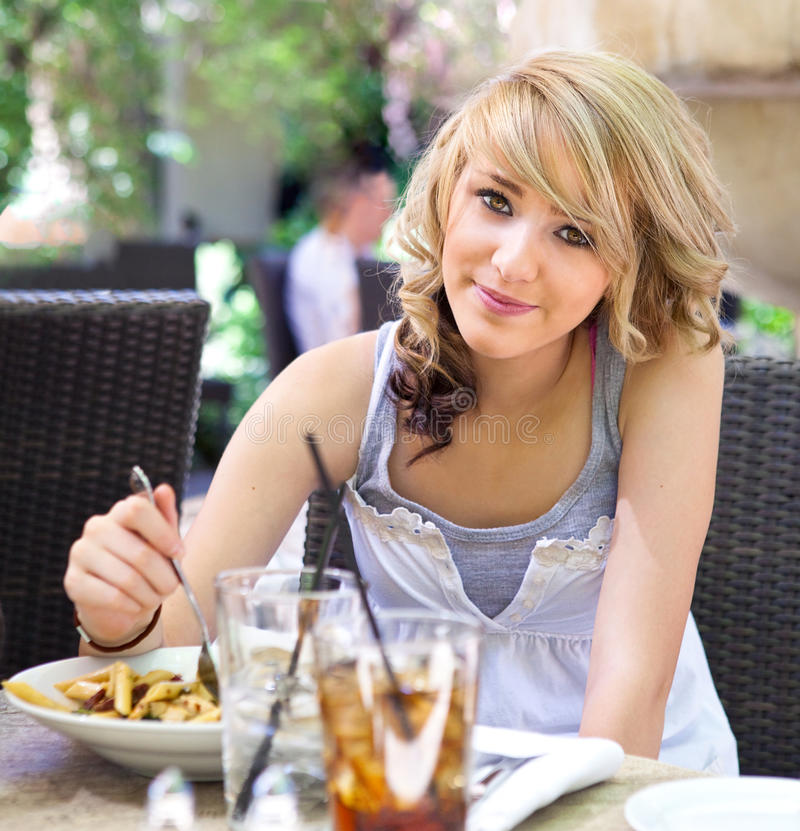 Cute Girl Eating Pasta at Outdoor Cafe royalty free stock photos