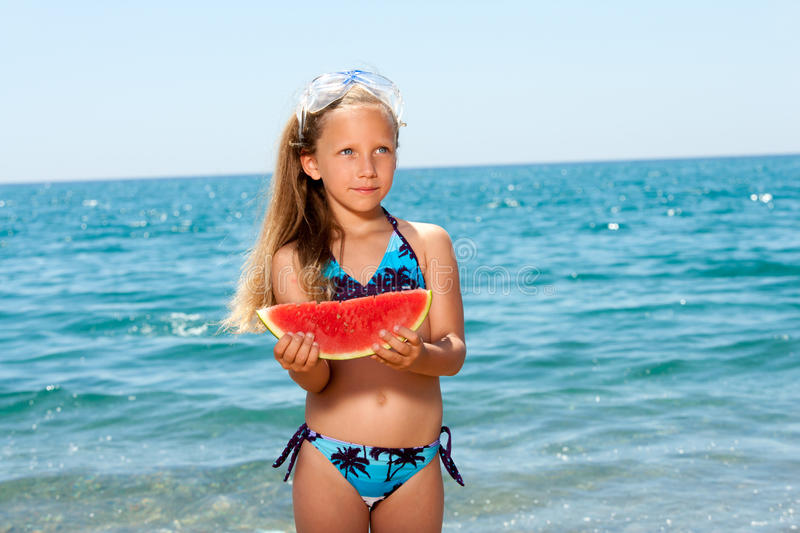 Cute girl eating watermelon on beach. stock images