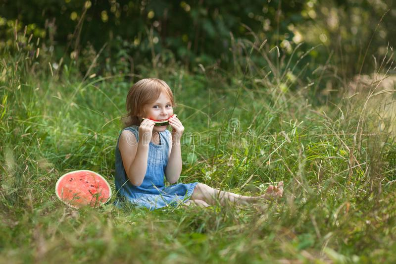 Cute girl eating watermelon in the summer outdoor. Healthy snack for children. Happy child girl in summer dress sitting on the grass and holding in her hands a royalty free stock image