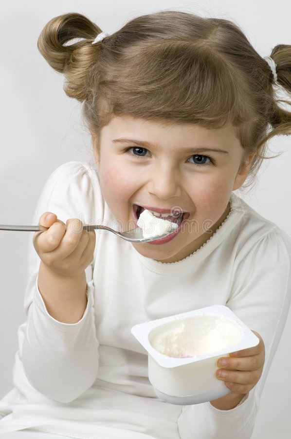 Cute girl eating yogurt royalty free stock photo