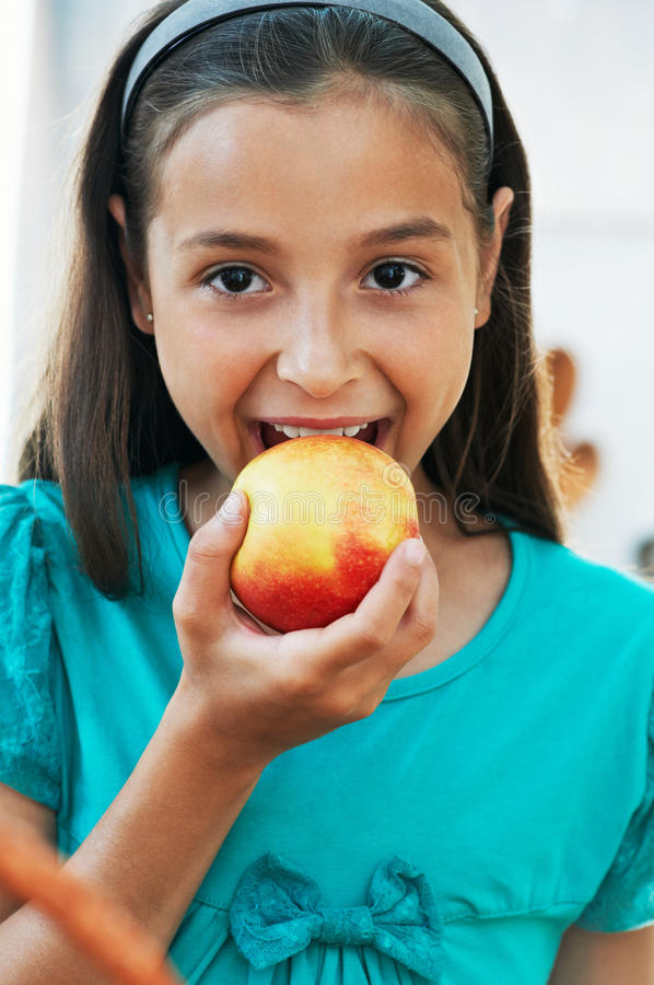Download Cute girl eats an apple stock photo. Image of hair, apple - 26106508