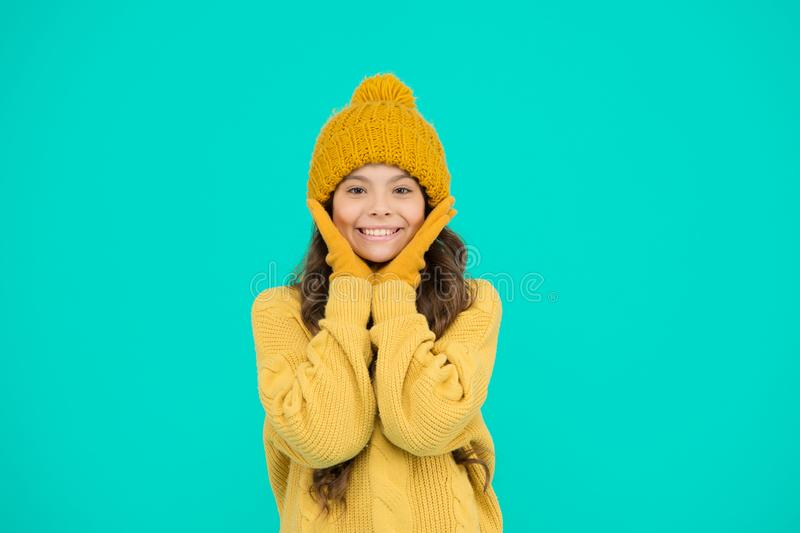 Cute girl enjoy winter style. Little kid wear knitted hat. Stay warm. Small child wear hat and sweater. Cold weather royalty free stock image