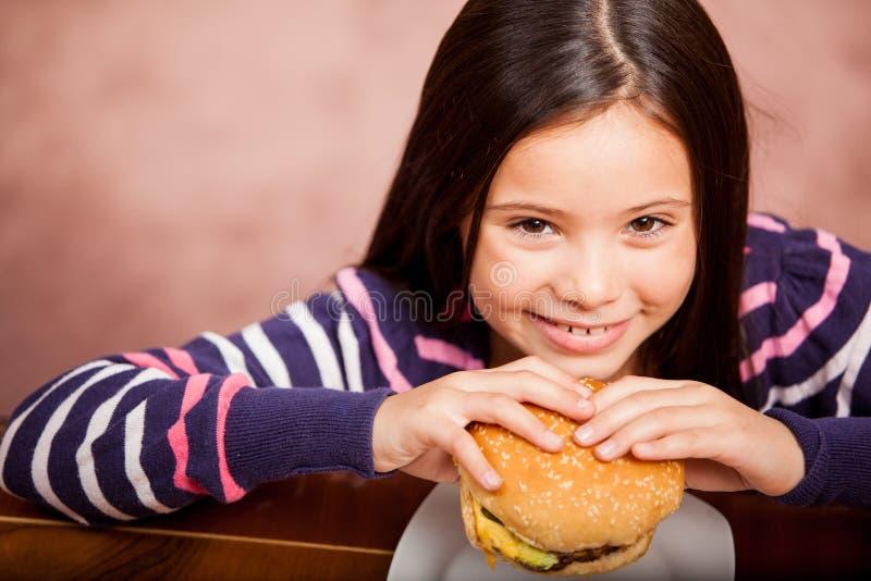 Cute Girl Enjoying A Hamburger Stock Image