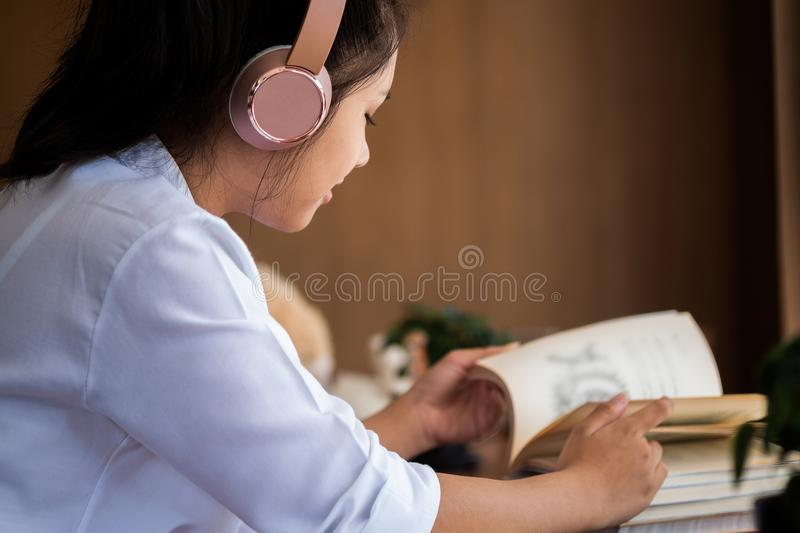 Cute girl enjoys listens to music in headphones in home, children concept, education concept royalty free stock photo