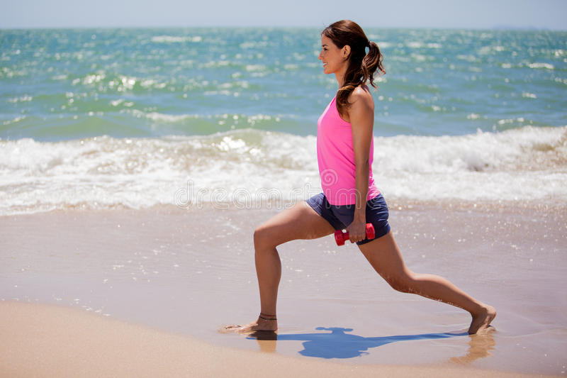 Cute girl exercising at the beach. Pretty young woman in sporty outfit lifting some weights at the beach stock image