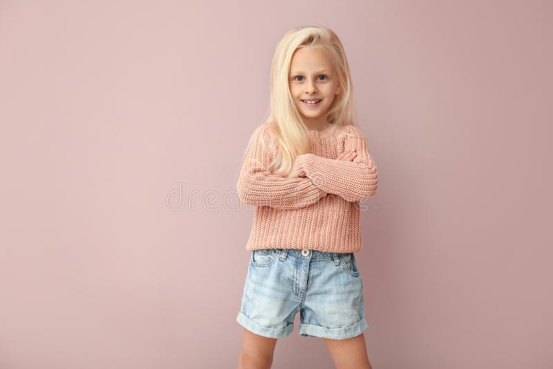 Cute girl in fashionable clothes on color background royalty free stock photos