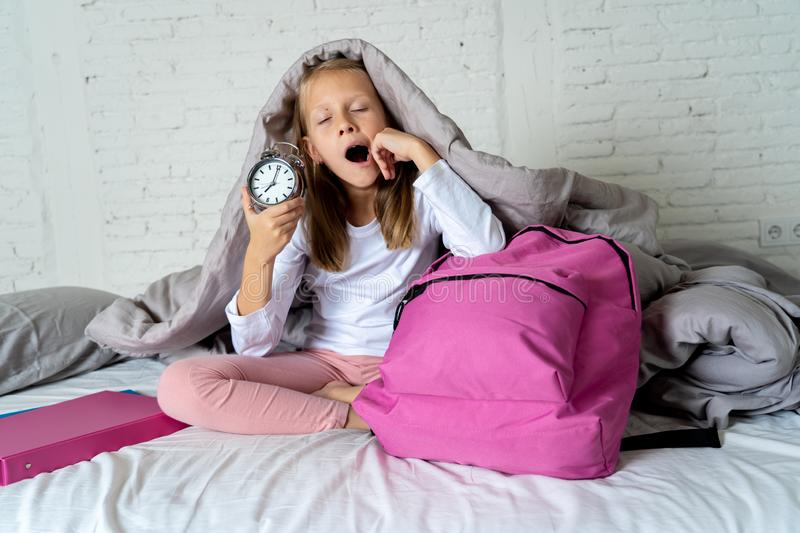 Cute girl feeling very tired early in the morning not wanting to get ready for school. Beautiful blonde little girl sad sleepless and angry showing alarm clock royalty free stock photography