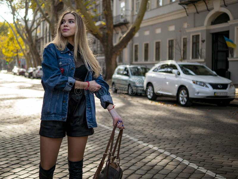 Cute girl with flowing hair in a denim jacket standing on the street with parked cars.  stock photos