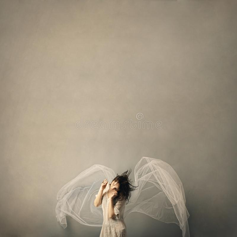 Cute girl in the form of an angel posing on a gray background. stock photos