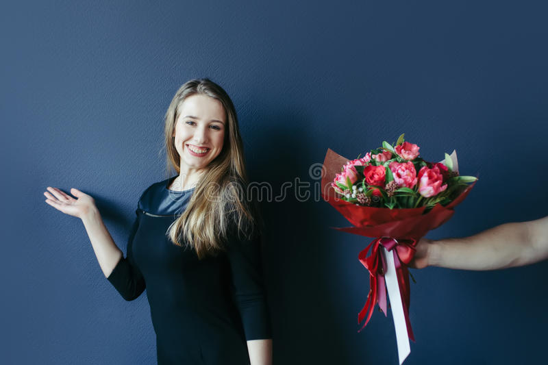 Cute girl getting bouquet of red tulips. Boyfriend giving tulips. royalty free stock image