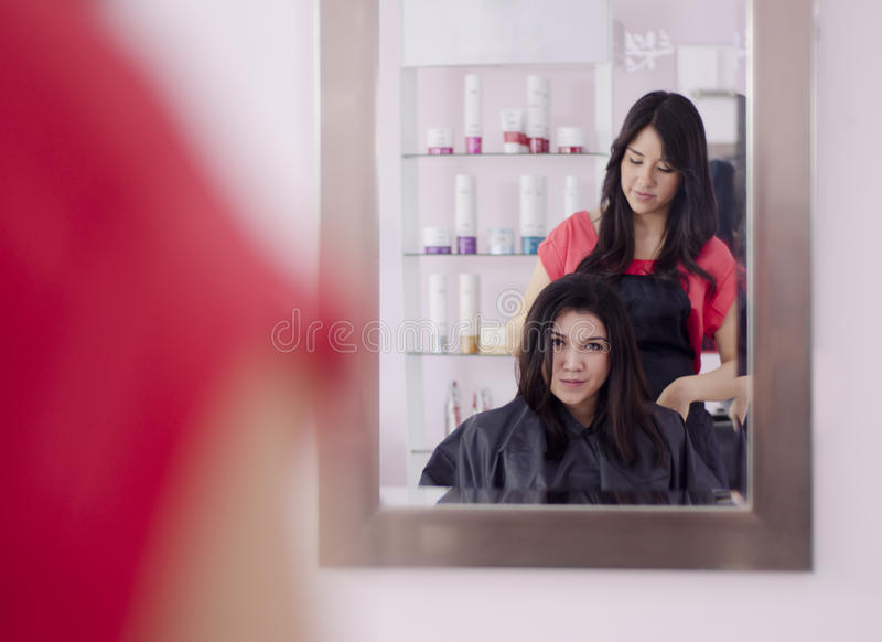 Cute girl in a hair salon. Young beautiful women getting her hair done and looking at a mirror in a hair salon royalty free stock photography