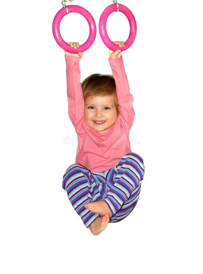 Cute girl hangs from rings royalty free stock image