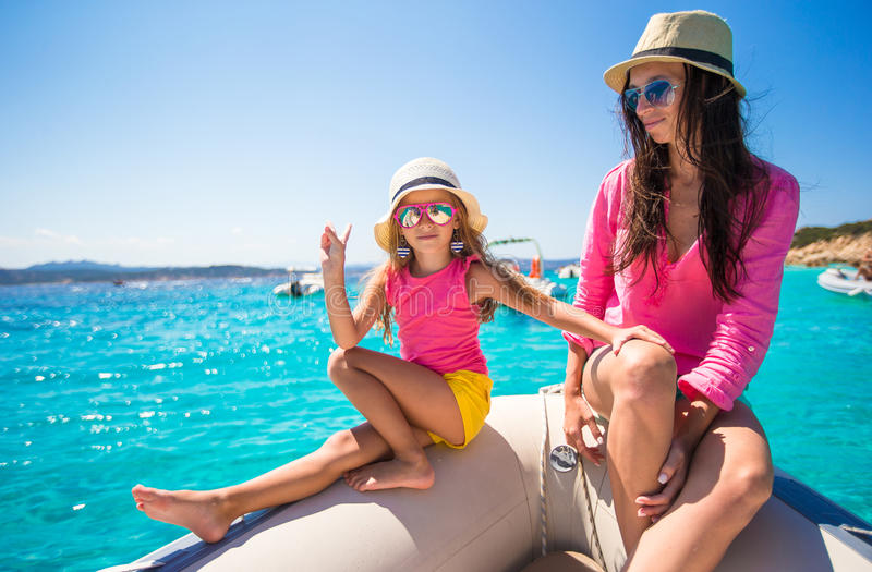 Cute girl and happy mom during vacation on boat in. Young mother with her adorable baby girl resting on a big boat stock image