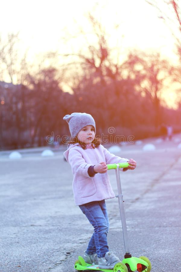 Cute girl in a hat, coat and jeans riding a three-wheeled scooter. Evening spring city sunset. Denim, single, child, tricycle, square, outdoor, town, street royalty free stock photos