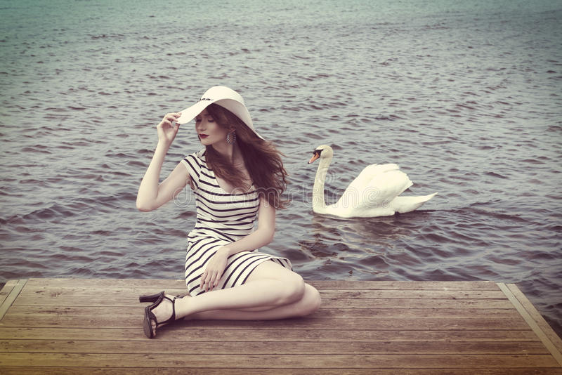 Cute girl with hat and near a swan . vintage color. Pretty woaman with hat , sitting on the lake bridge , she has a beautiful white swan near her in the water royalty free stock images