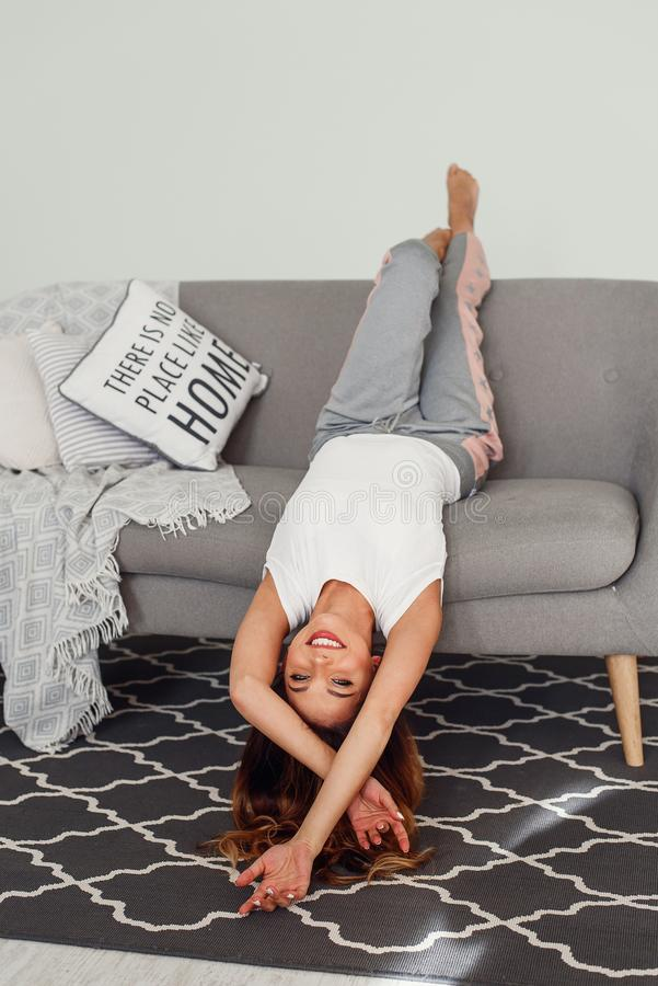 Beautiful woman relaxing on a grey couch with head upside down. Cute girl having fun at cozy home in lazy day. Cute girl having fun at cozy home in lazy day. A royalty free stock images