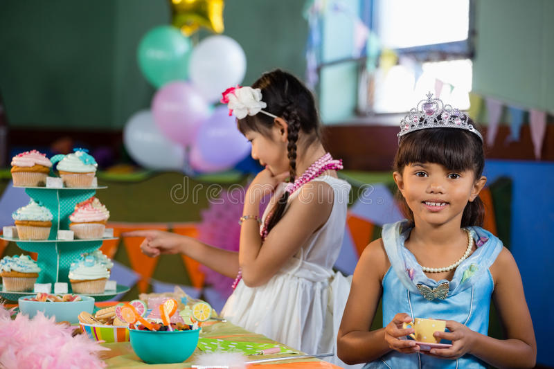 Cute girl having tea at table during birthday party stock photography