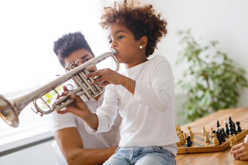 Girl with her father learning trumpet royalty free stock photos