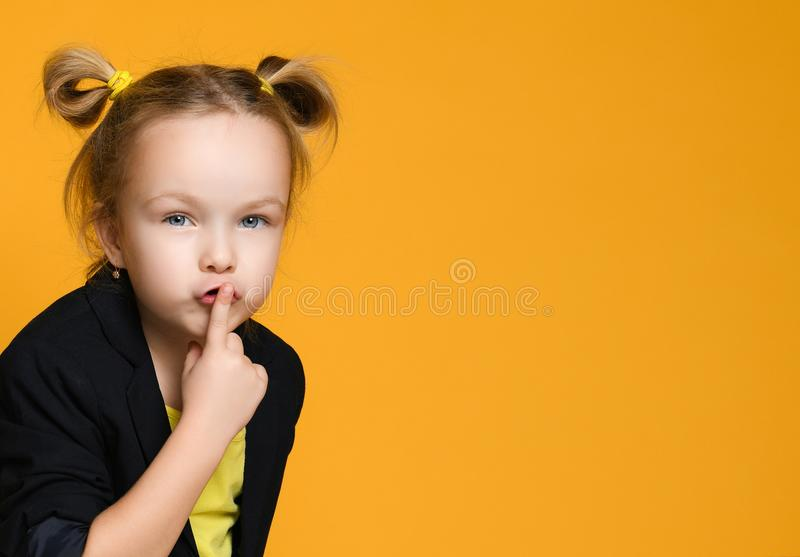 Cute girl with her finger over mouth saying `Shh!` royalty free stock images