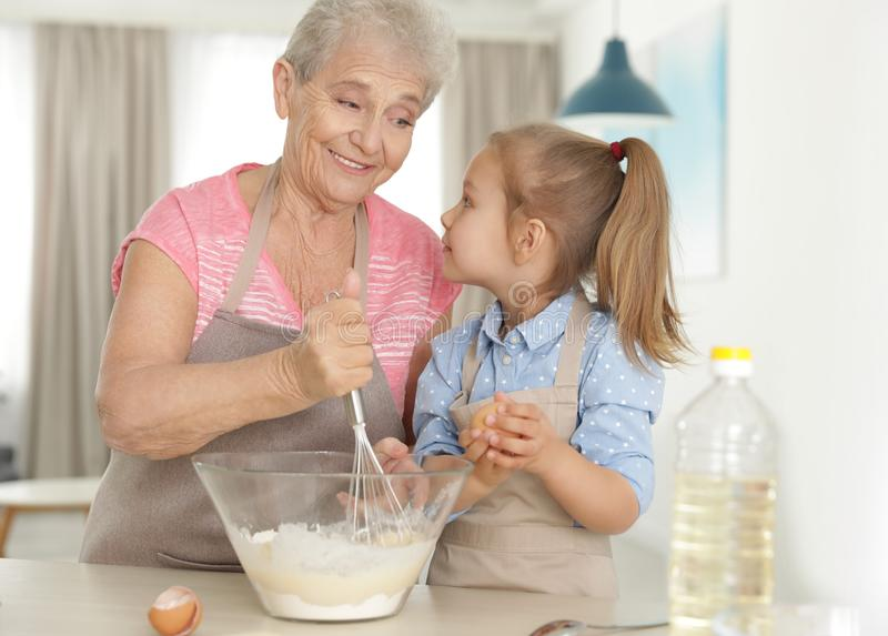 Cute girl and her grandmother cooking stock photography