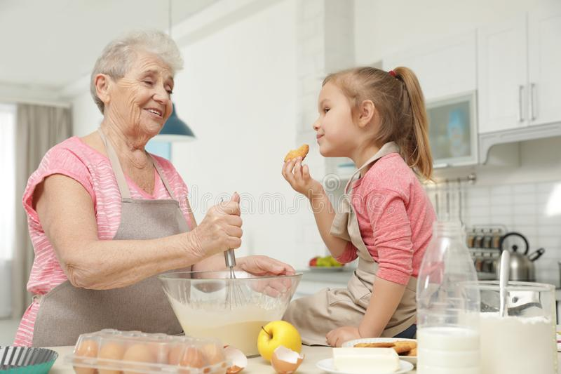 Cute girl and her grandmother cooking royalty free stock images