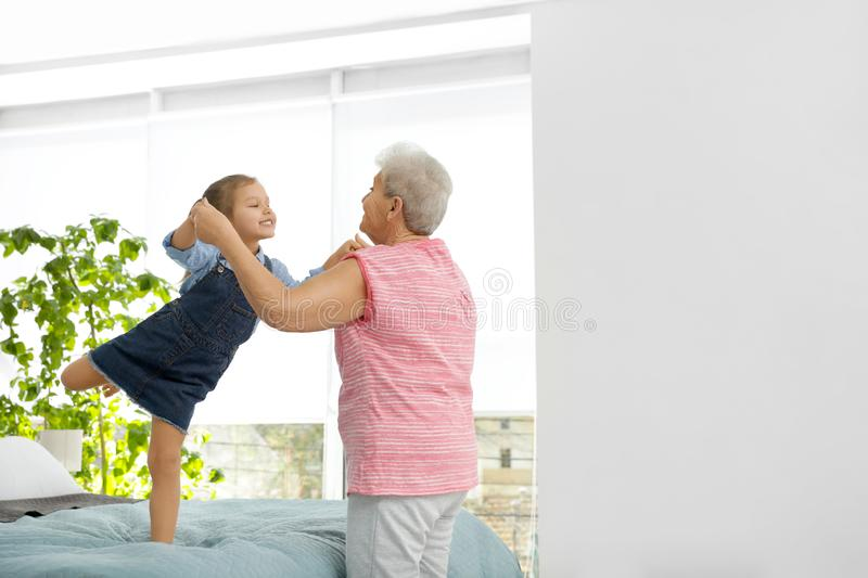 Cute girl and her grandmother playing together stock photography