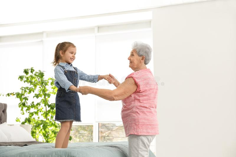 Cute girl and her grandmother playing together stock images