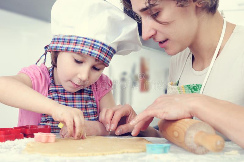 Cute girl with her mother bake cookies at home. Cute little girl with her mother bake cookies at home kitchen stock photo